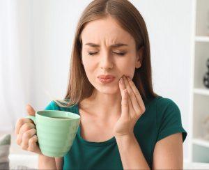 woman with coffee mug touching her cheek in pain