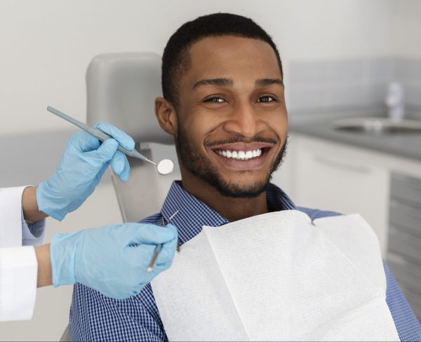 young adult man smiling in the dental chair as the dentist uses tools to examine his mouth